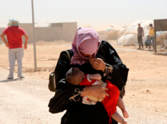 a_syrian_refugee_woman_carries_her_baby_as_they_wa_502975e190