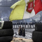 A priest speaks through a megaphone to riot police and anti-government protesters at the site of recent clashes in Kiev