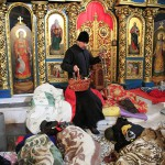 A clergyman walks as people rest inside Mikhailovsky Zlatoverkhy Cathedral, which serves as a temporary shelter and a first-aid post for anti-government protesters, in Kiev
