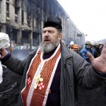 An Otrthodox priest gestures after clashes between anti-government protesters and riot police in the Independence Square in Kiev