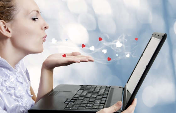 Concept - young attractive woman love laptop computer or internet boyfriend. She sending Air kiss to screen. Dating site